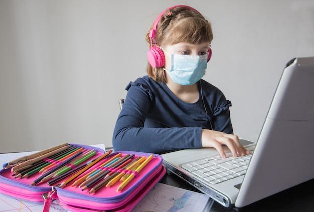 Hübsches schulmädchen, das hausaufgabenmathematik während ihres online-unterrichts zu hause studiert, soziale distanz während der quarantäne,