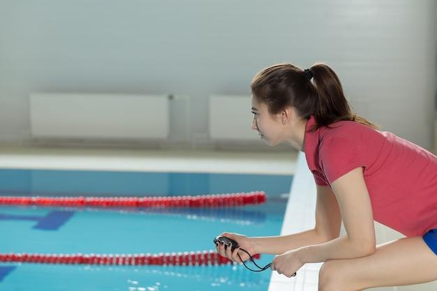 Hübsches schwimmtrainer-trainermädchen mit stoppuhr in der nähe des pools. exemplar