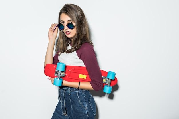 Hübsches skatermädchen in der freizeitkleidung und in der schwarzen sonnenbrille, die rotes skateboard lokalisiert auf weißer wand hält