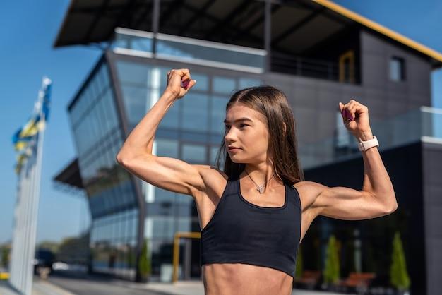 Hübsches sport weibliches modell, das morgenstrecken vor modernem glasgebäude, lebensstil tut