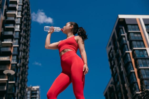 Hübsches sportliches mädchen mit braunem pferdeschwanz, das rote leggins und oberes trinkwasser von plastikflasche trägt. ruhende sportliche frau. verschwommener stadthintergrund. low angle shot.