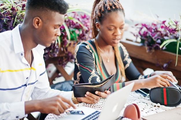 Hübsches stilvolles afroamerikanerpaar, das im straßencafé mit laptop mit kreditkarte und geld von der brieftasche sitzt.