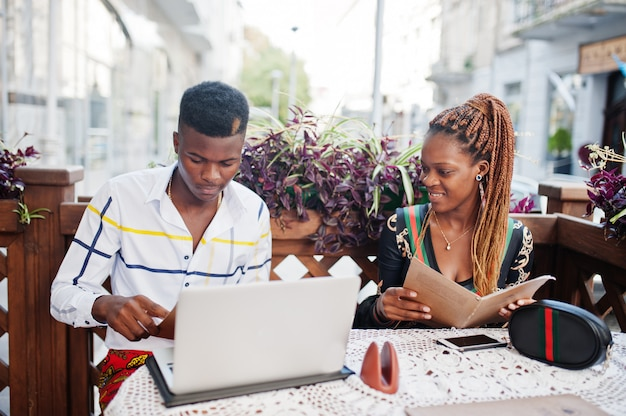Hübsches stilvolles afroamerikanerpaar, das im straßencafé mit laptop sitzt und gericht am menü wählt.