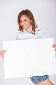 Hübsches studentenmädchen, das spaß hat und weißen leeren schildhintergrund hält.
