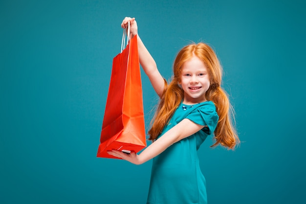 Hübsches, süßes kleines mädchen in blauer kleidung mit langen roten haaren hält paket