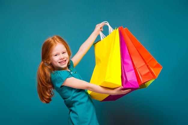 Hübsches, süßes kleines mädchen in blauer kleidung mit langen roten haaren kümmert sich um verschiedene pakete
