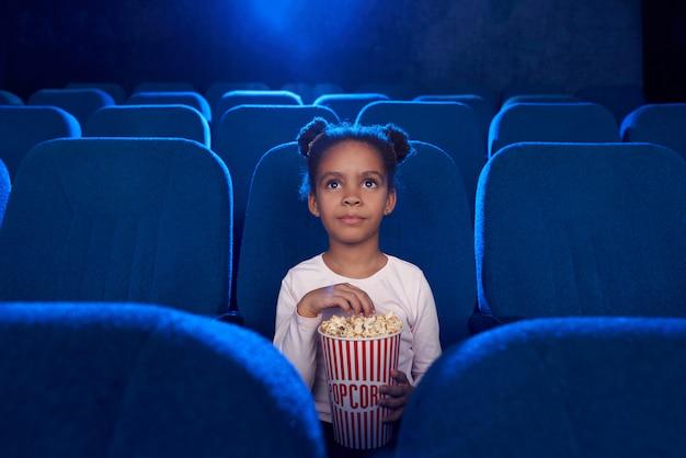 Hübsches süßes mädchen, das mit popcorn-eimer im kino sitzt.