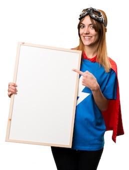 Hübsches superheldmädchen, das ein leeres plakat hält