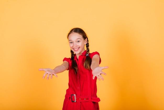 Hübsches teenager-mädchen, das vor der kamera lächelt und auf gelbem hintergrund fröhlich aussieht. positive gefühle