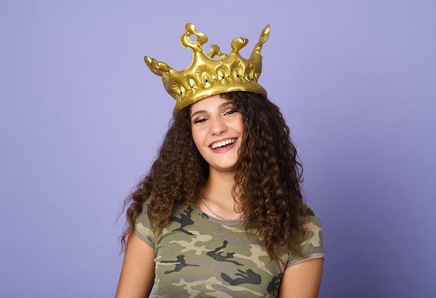 Hübsches teenager-mädchen mit goldener krone auf violetter wand