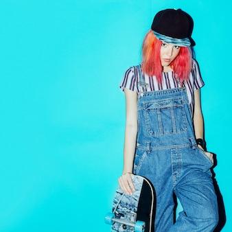 Hübsches teenager-skate-mädchen mit rosa haaren urban style jeans fashion