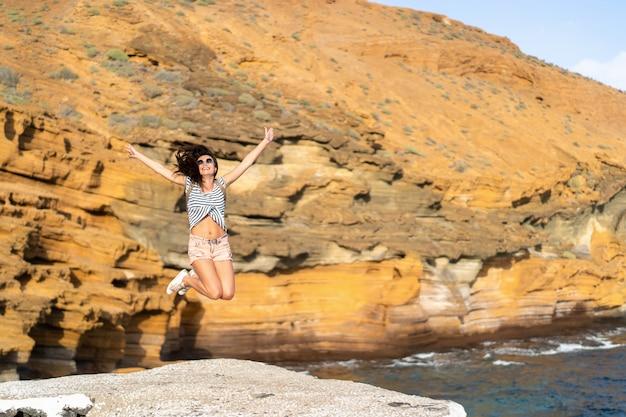 Hübsches touristisches brunettemädchen, das nahes meer des spaßes im freien hat.