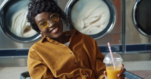 Hübsches und glückliches afroamerikanisches mädchen, das im wagen sitzt und orangensaft mit stroh trinkt, sich ausruht und darauf wartet, dass kleidung gewaschen wird. stilvolle frau nippt getränk im wäscheservice-raum.