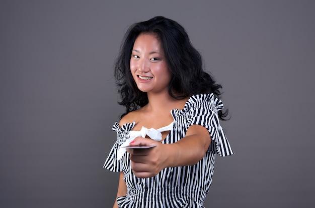 Hübsches und nettes junges chinesisches mädchen, das karte mit direktem blick und lächeln anbietet