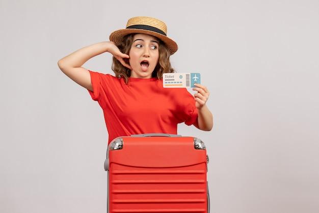 Hübsches urlaubsmädchen mit ihrem koffer mit fahrkarte