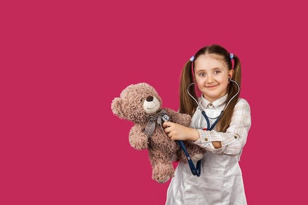 Hübsches vorschulkind, das ein bärenherz mit einem stethoskop hört