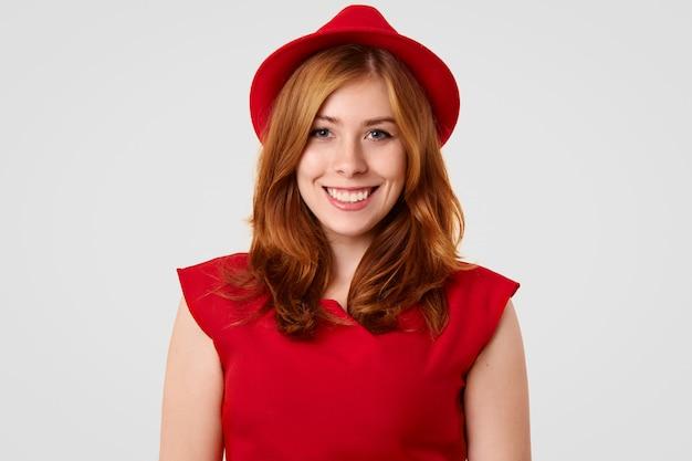 Hübsches weibliches model mit positivem lächeln, gekleidet in eleganten roten hut und bluse, verabredung mit freund