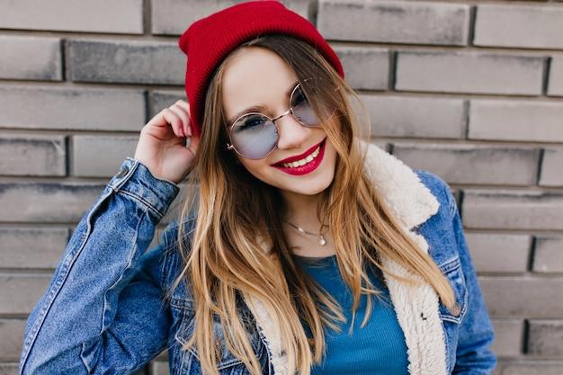 Hübsches weißes mädchen mit fröhlichem lächeln, das spaß am kalten frühlingstag hat. außenporträt der freudigen blonden frau trägt blaue brille und roten hut.