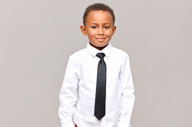 Hüfte auf hübschen ordentlichen dunkelhäutigen männlichen grundschüler, der isoliert gekleidet in weißem sauberem gebügeltem hemd und schwarzer eleganter krawatte posiert, bereit für den schulbesuch, lächelnd