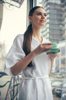Hüfte einer friedlichen entspannten frau im bademantel, die eine tasse tee auf dem teller hält und lächelt, während sie in der nähe des fensters steht und wegschaut