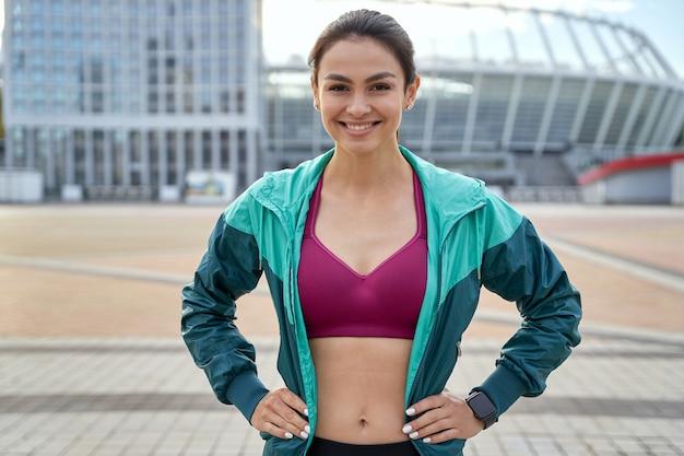 Hüfte einer lächelnden dame in sportkleidung, die in der stadt steht und in die kamera schaut gesundes lebensstilkonzept
