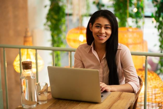 Hüfte einer ruhigen, zufriedenen jungen dame, die lächelt, während sie in einem café mit einem glaskrug wasser in der nähe ihres geräts an ihrem laptop arbeitet working