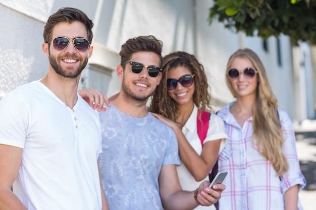 Hüftenfreunde, die den smartphone sich lehnt an der wand betrachten