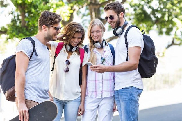 Hüftenfreunde, die draußen smartphone betrachten