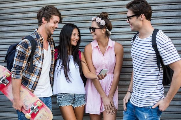 Hüftenfreunde, die smartphone betrachten und an der rolltür sich lehnen