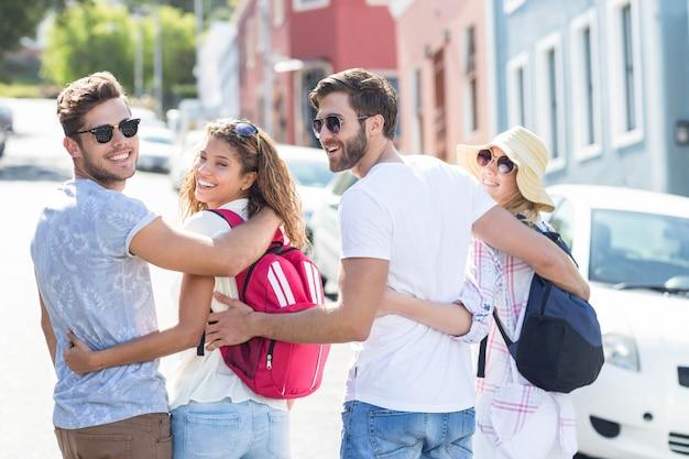 Hüftenfreunde mit den rucksäcken, welche zurück der kamera in der stadt betrachten