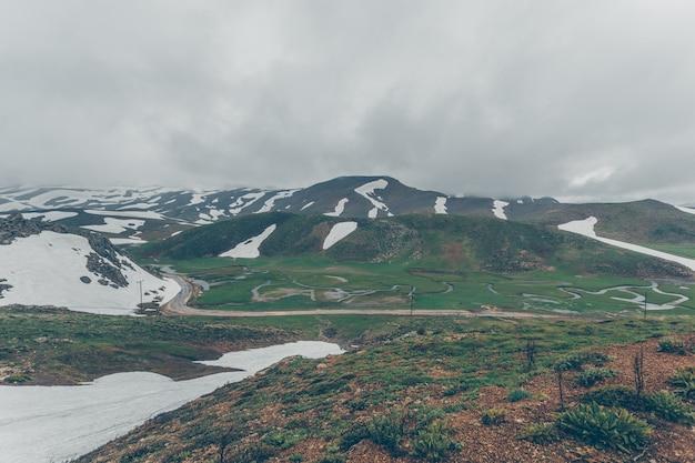 Hügel, die am wolkentag zur hälfte mit schnee bedeckt waren