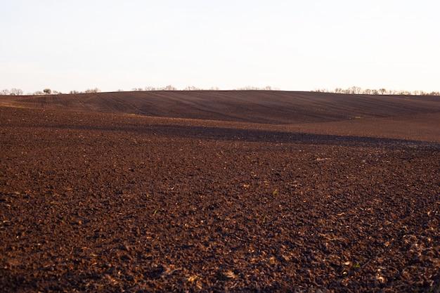 Hügelige braune feldlandschaft, landwirtschaftliches frühlingsfeld.