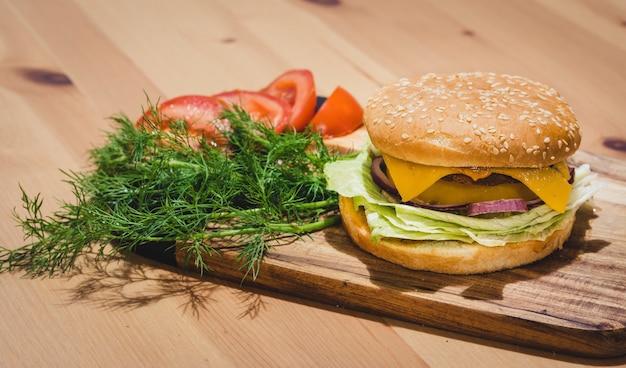 Hühnchen-burger mit frischen tomaten und dills, auf holzbrett mit platz zum kopieren
