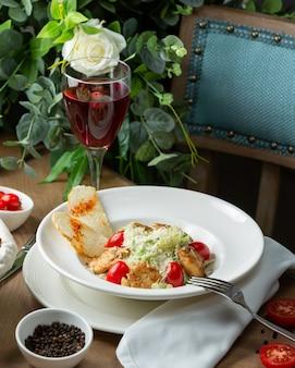 Hühnchen caesar salat mit einem glas wein