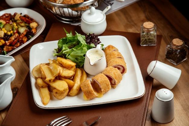 Hühnchen cordon bleu mit kartoffeln in ländlichen salat und sauce auf teller