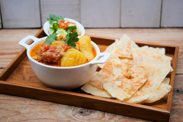 Hühnchen-curry-schüssel serviert mit roti,