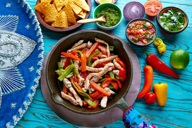 Hühnchen-fajitas in einer pfanne mit chili und mexikaner