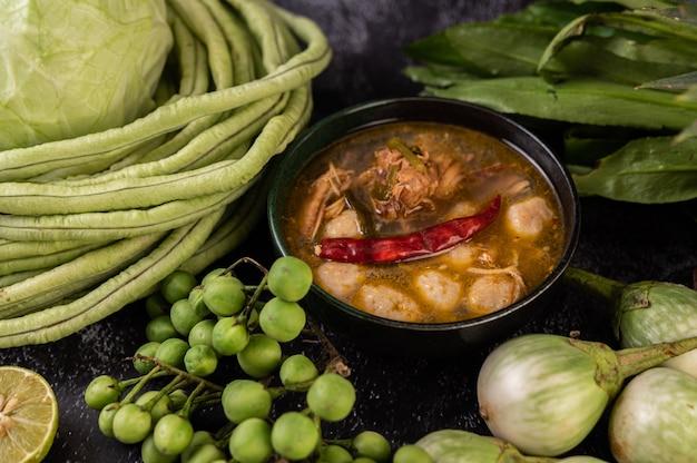 Hühnchen-fleischbällchen-sauce mit auberginen, chili, langen bohnen, kohl und auberginen.