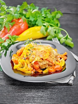 Hühnchen gedünstet mit tomaten, gelben und roten paprika und käse in einem teller auf serviette, thymian, petersilie und knoblauch auf schwarzem holzbretthintergrund