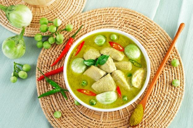 Hühnchen-grünes curry mit thailändischem essen auf holzteller, geschnittene hühnertierfilets, geviertelte auberginen, erbsen-auberginen, basilikumblätter, pfeffer und kokosmilch. grüne currypaste.