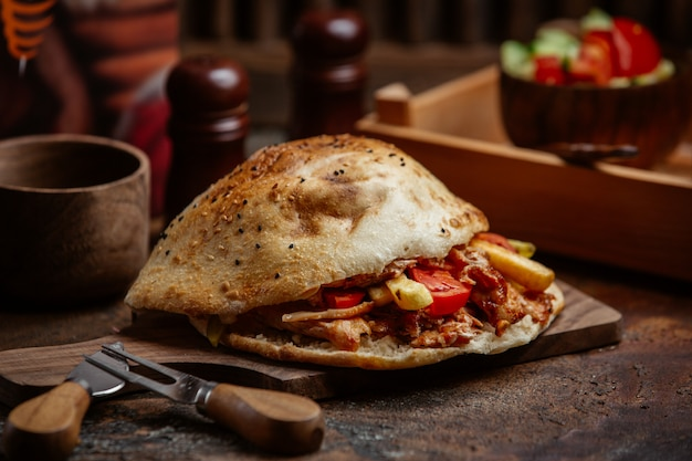 Hühnchen-kebab-döner mit kartoffeln, sauce, tomate im fladenbrot
