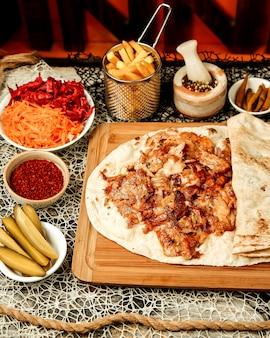 Hühnchen-kebab-döner, serviert in fladenbrot mit pommes und gurken