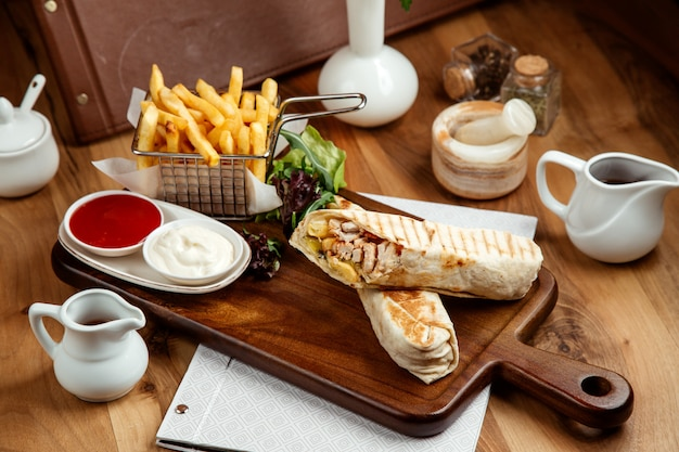 Hühnchen-shawarmin-grube mit pommes-frites-ketchup-mayo und salat auf dem tisch