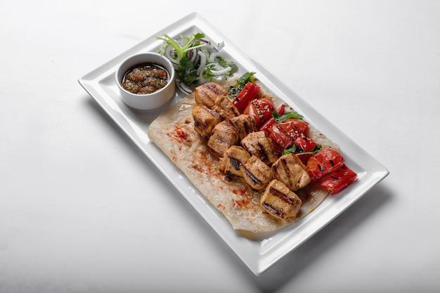 Hühnchen-spieße auf fladenbrot mit marinierter zwiebelsauce und gebackenem paprika auf einem weißen teller auf einem weißen teller