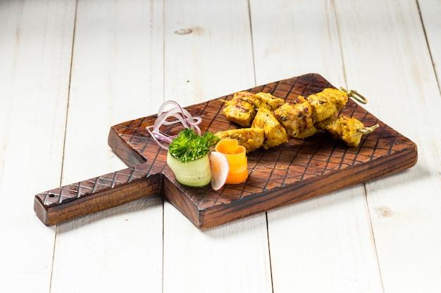 Hühnchen-spieße im asiatischen stil auf dem holzbrett