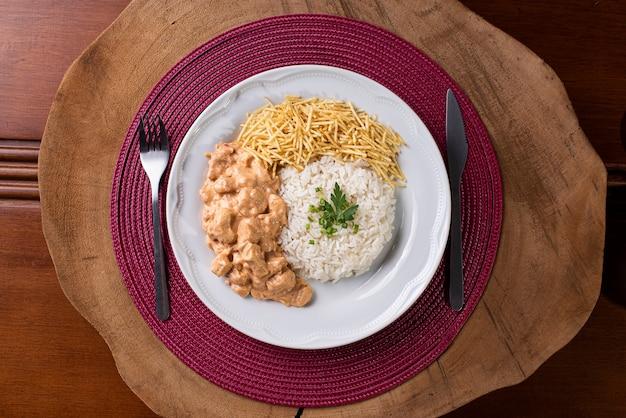 Hühnchen-stroganoff mit reis, salat und kartoffelstroh