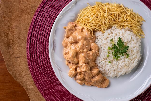 Hühnchen-stroganoff mit reis, salat und kartoffelstroh.