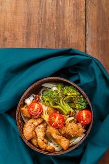 Hühnchen-udon in japanischer sauce auf einem teller mit kokosnussschalen auf einer blauen serviette vertikales foto
