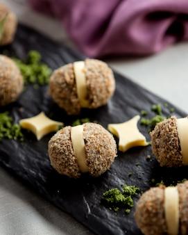 Hühnchenbällchen mit käse und mit geriebener nuss bestreut