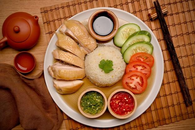 Hühnchenreis aus hainan wird mit chilisauce, einer garnitur aus tomaten- und gurkenstreifen und einer sauce aus sojabohnenpaste serviert. ansicht von oben